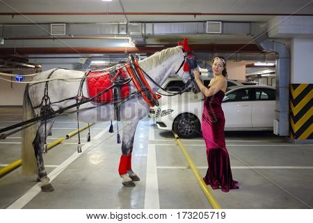 Woman in long dress poses with horse in harness in underground parking