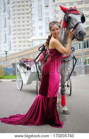 Pretty woman in red dress stands near horse with coach near residential building
