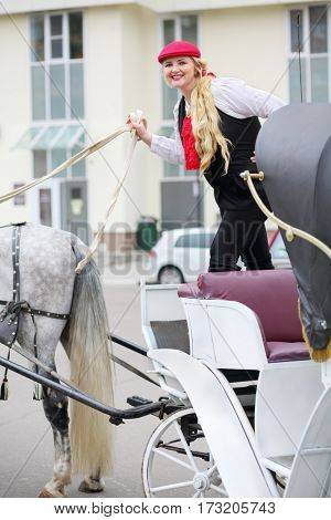 Happy coachman blonde on trestles holds reins on couch with horse near residential buildings