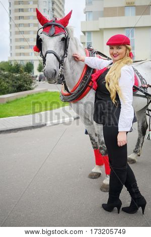 Smiling coachman woman stands with horse in red harness near residential buildings