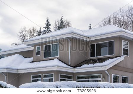 Top of residential house in snow on winter cloudy day