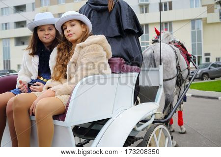 Two girls in hats pose in coach with coachman and horse near residential buildings