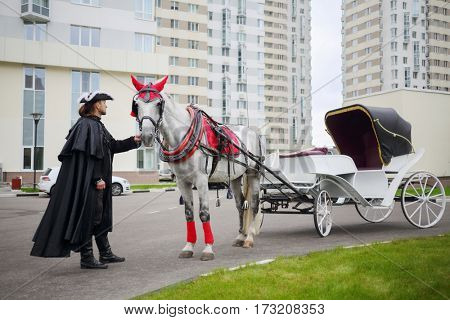 Coachman in black cloak stands near couch with horse near residential buildings
