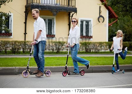 Man, woman and girl ride on scooters in front of house on street.