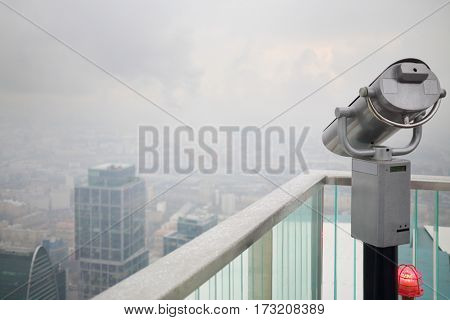 Binoculars on viewing platform on rainy day and office buildings in fog in Moscow