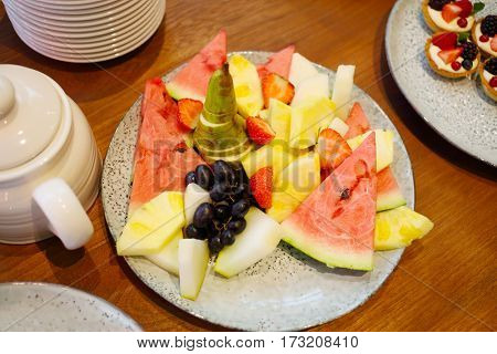 Pieces of fruit on plate, watermelon, grapes, pineapple, melon, pear, strawberry
