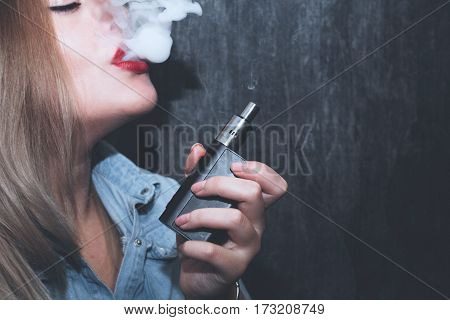 Beautiful young blonde girl smokes electronic cigarette