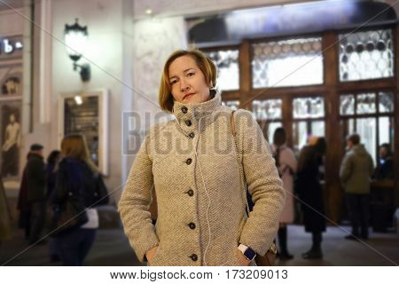 Woman in coat with bag stands on street near of theater with people out of focus