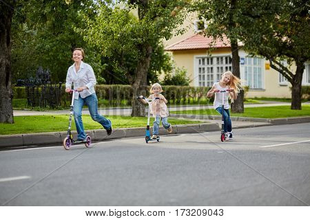 Woman and two girls ride on scooters on street, focus on little girl.