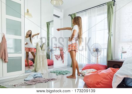 10 years old pre teen girl choosing outfit in her closet. Messy in the bedroom, clothing on the floor. Teenager is dressing up and dancing in the morning.