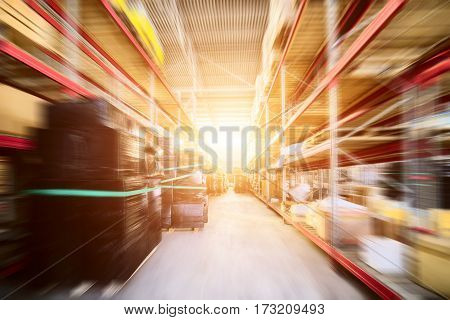 Warehouse industrial and logistics companies. Long shelves with a variety of boxes and containers. The effect of motion blur. Bright sunlight.