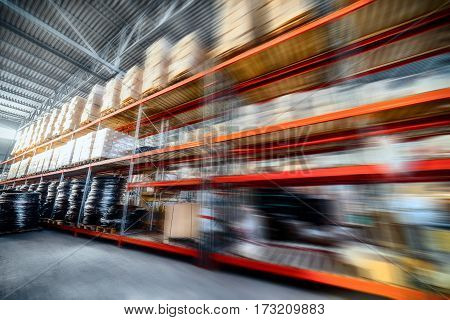 Warehouse industrial goods. Large long racks. Cardboard boxes and coiled plastic tube. Motion blur effect.