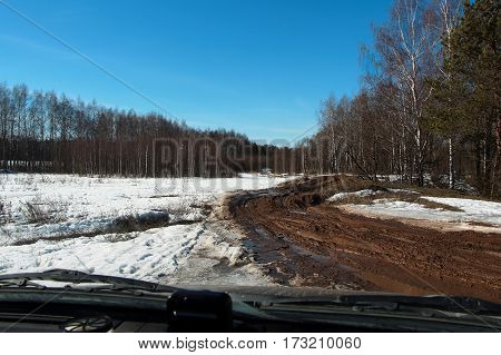 Spring thaw. Country road through the windshield of the car