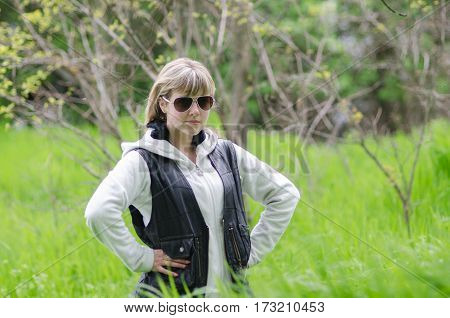 a girl on a forest glade stands in a grass