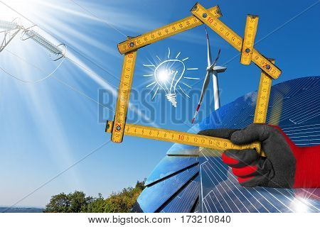 Hand with work glove holding a wooden ruler in the shape of house with a solar panel wind turbine power line and a illustration of a light bulb