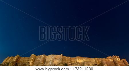 Details of Jodhpur fort at night. The majestic fort perched on top with clear blue starry sky above. Orion constellation and the Pleiades. Travel destination in Rajasthan India.