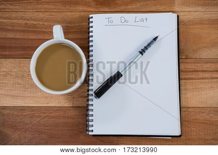 Cup of tea with diary and pen on table