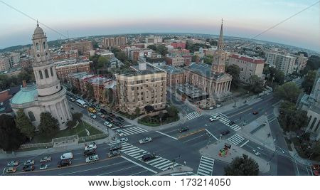 Cityscape with edifices of All Souls Church and National Baptist Memorial Church on street with traffic at summer evening in Washington DC. Aerial view
