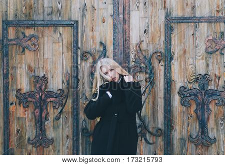 Beautiful young blond woman in the jacket near old wooden house