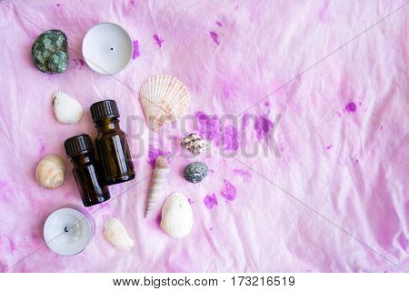 Spa concept: seashells and candles and aroma oils on the pink textile background