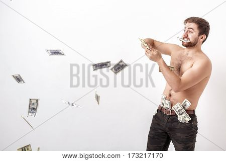 young handsome brunette man with a beard holding a lot of hundred dollar bills and throws them into the air. money and wealth