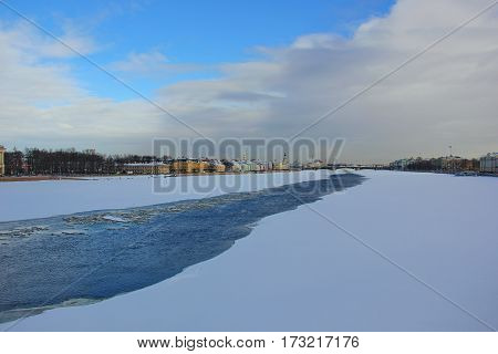 Russia, Saint-Petersburg, 24 Feb 2017. the river Neva is covered with ice and snow, in the middle of the punched narrow passage relative to the width of the river, opening with blue cold water in which ice floating on the background some of the main archi