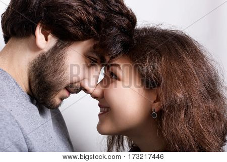 Happy couple in love touching noses smiling and looking at each other`s words. Close-up nose to nose. Couple in love touching noses. Young couple standing close face to face and touching by noses.