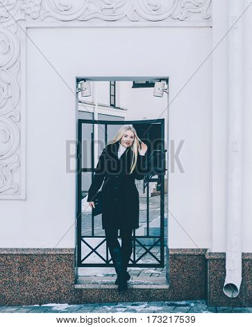 beautiful blonde woman in street on background city gates