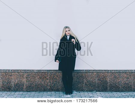 Young beautiful blonde girl near the building wall