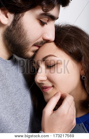 A sensual photo of loving couple standing close to each other. A young woman leaning to her boyfriend. A bearded hipster touching his girlfriend`s forehead with his lips. Feelings and relationships.