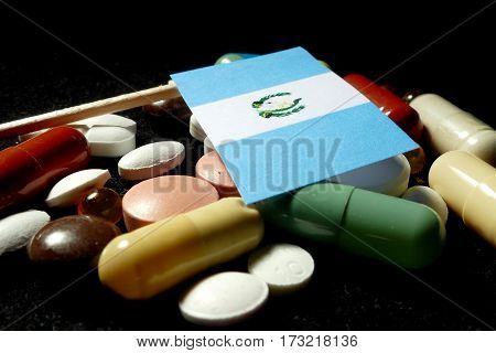 Guatemalan Flag With Lot Of Medical Pills Isolated On Black Background