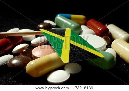 Jamaican Flag With Lot Of Medical Pills Isolated On Black Background