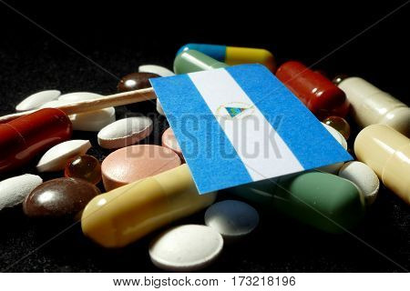 Nicaraguan Flag With Lot Of Medical Pills Isolated On Black Background
