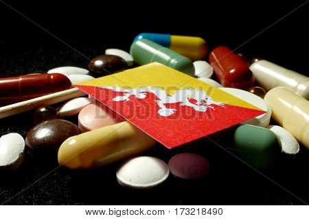 Bhutanese Flag With Lot Of Medical Pills Isolated On Black Background