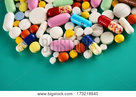 Multicolored Pills And Tablets On Green Background