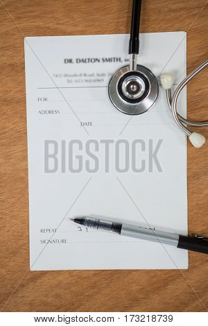 Close-up of doctor letterhead with stethoscope and pen in wooden table