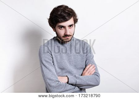 A portrait of serious young bearded guy with stylish hairstyle dressed in casual sweater standing crossed hands isolated over white background looking serious and confident. People and lifestyle.