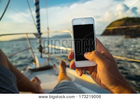 Rest on a yacht with a phone in hand. Summer leisure. Male lying on the deck and enjoy your smartphone. The guy doing the photo feet on the background seascape and yachts.