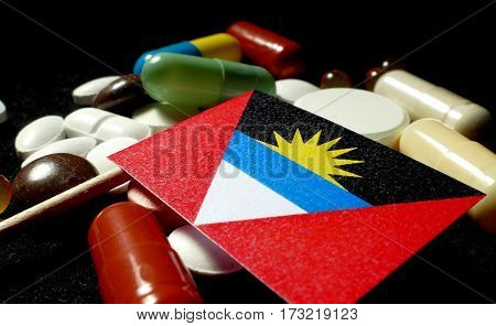 Antigua And Barbuda Flag With Lot Of Medical Pills Isolated On Black Background