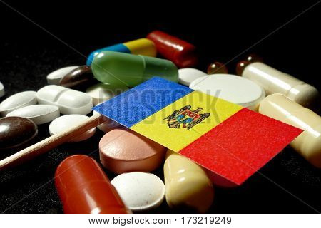 Moldovan Flag With Lot Of Medical Pills Isolated On Black Background