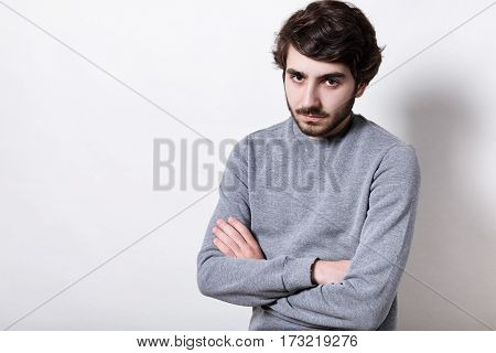 A stylish young guy with modern hairstyle and dark beard having tired and angry expression standing crossed hands over white background. People emotions and feelings. Man showing negative emotion