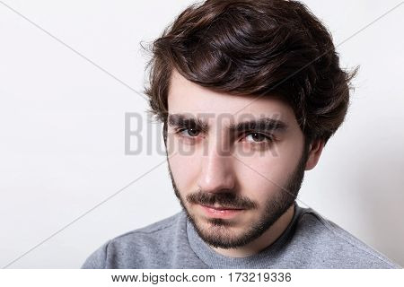 Headshot of handsome hipster with black beard and stylish hair looking at camera with serious face expression squinting his eyes. Portrait of masculinity. People and emotions.