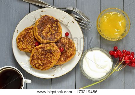 Homemade spicy pumpkin pancakes with honey and sour cream fritters, top view