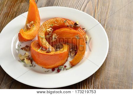 Slices of pumpkin baked in the oven with walnuts and spices