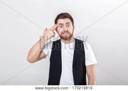 finger to his temple. young handsome man with a beard in a white shirt and a black waistcoat shooting with finger on his head.