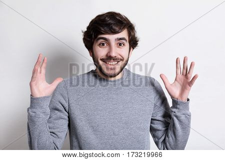 Human face expressions and emotions. Portrait of young hipster with beard and modern hairstyle smiling at camera with arms outstretched isolated over white background. Happy expression of a guy