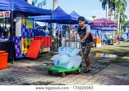Labuan,Malaysia-Feb 25,2017:Unidentified food & drink vendor with Ice cubes in Labuan night market in Labuan,Malaysia.Night market merchants setup multi-coloured & brightly lit makeshift stalls where they sell everything from food & drink.