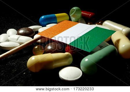 Ivory Coast Flag With Lot Of Medical Pills Isolated On Black Background