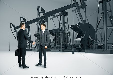Businessmen shaking hands on light background with oil derricks. Partnership concept. 3D Rendering
