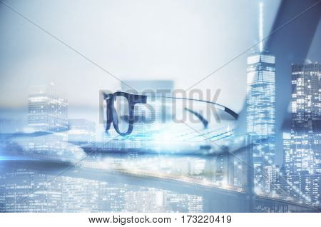 Side view of laptop with glasses on abstract city background. Work concept. Double exposure